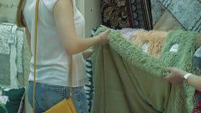 Het jonge mooie meisje kiest een doek stock video