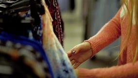 Het jonge mooie meisje kiest kleren in een supermarkt stock video