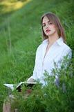 Het jonge mooie meisje kijkt zorgvuldig zittend op weidewi Stock Foto's