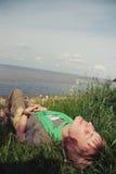 Het jonge mooie meisje liggen met haar ogen sloot en een glimlach op zijn gezicht het groene gras de baai warme zonnige dag Stock Foto's