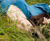 Het jonge mooie meisje ligt op een gras royalty-vrije stock afbeelding