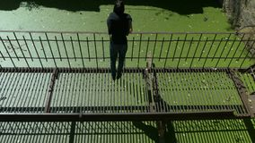 Het jonge mooie meisje loopt op dunne geruïneerde roestige metaalbrug over groen water stock videobeelden