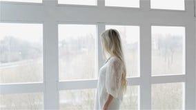 Het jonge mooie meisje met een lang blondehaar bevindt zich dichtbij het venster stock footage