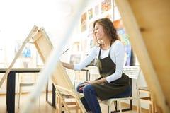 Het jonge mooie meisje met krullend haar gekleed in witte blouse, bruine schort en jeans schildert een beeld bij de schildersezel royalty-vrije stock foto