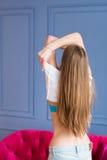 Het jonge mooie meisje met lang bruin haar stijgt haar wit hemd op royalty-vrije stock foto's
