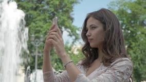 Het jonge mooie meisje met lang haar neemt een beeld van zich op de telefoon In het stadspark, dichtbij de fontein stock video