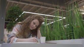 Het jonge mooie meisje met rood haar drinkt een latte van een stro en neemt nota's in een notitieboekje stock videobeelden