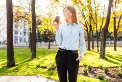 Het jonge mooie meisje, in officiële kleren, drinkt koffie, luistert stock afbeelding