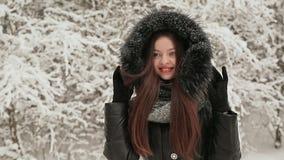 Het jonge mooie meisje op de achtergrond van snow-covered sparren in warme de winterkleren met wordt een kap beschut van stock video