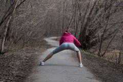 Het jonge mooie meisje opwarmen vóór stoot in het Park aan stock fotografie