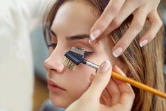 Het jonge, mooie meisje, past mascara op de wimpers in een schoonheidssalon toe royalty-vrije stock afbeelding