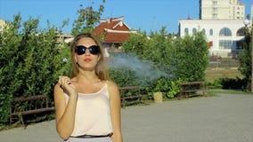 Het jonge mooie meisje rookt elektronische sigaret stock footage