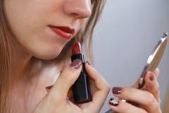 Het jonge mooie meisje schildert haar lippen met rode lippenstift en holdi Stock Afbeelding