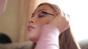 Het jonge mooie meisje schildert wimpers vóór een spiegel, close-up stock footage