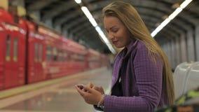 Het jonge mooie meisje schrijft berichtgebruik een smartphone stock videobeelden
