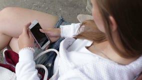 Het jonge mooie meisje schrijft sms gebruikssmartphone stock videobeelden