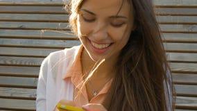 Het jonge mooie meisje schrijft SMS op uw smartphone stock video
