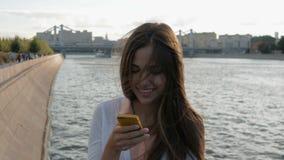 Het jonge mooie meisje schrijft SMS op uw smartphone stock videobeelden