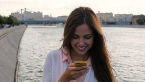 Het jonge mooie meisje schrijft SMS op uw smartphone stock footage