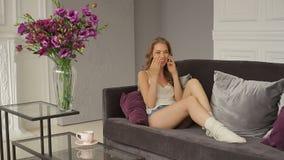 Het jonge mooie meisje in sleeveless blouse en borrels spreekt op telefoon stock footage