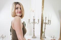 Het jonge mooie meisje stellen dichtbij spiegel in luxeflat in retro stijl stock fotografie