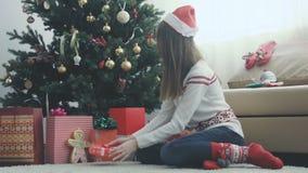 Het jonge mooie meisje verpakt een Kerstmisgift stock videobeelden