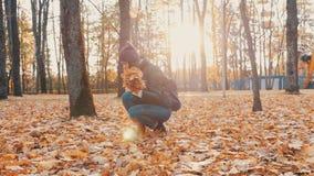 Het jonge mooie meisje verzamelt een boeket van gevallen bladeren in de herfstpark 50 fps stock video