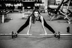 Het jonge mooie meisje werkt in de gymnastiek uit Royalty-vrije Stock Foto's