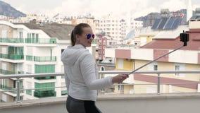 Het jonge mooie meisje wordt gefotografeerd op een smartphone terwijl status op het balkon van een flatgebouw stock video