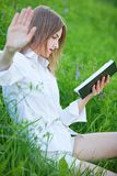 Het jonge mooie meisje zit op een open plek met een boeklezing, het maken Stock Afbeelding