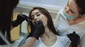 Het jonge mooie meisje zit in tandkabinet bij behandeling en het consultating stock video