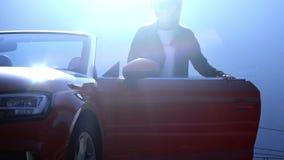 Het jonge mooie meisje in zwarte glazen en een leerjasje komt omhoog en zit in een rood convertibel tegen de achtergrond stock footage