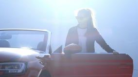 Het jonge mooie meisje in zwarte glazen en een leerjasje komt omhoog en zit in een rood convertibel tegen de achtergrond stock video