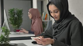 Het jonge mooie meisje in zwarte hijab zit in bureau en gebruikt smartphone Meisje in zwarte hijab op de achtergrond arabier stock footage