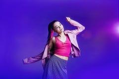 Het jonge mooie model stellen in roze licht op een grijze achtergrond royalty-vrije stock fotografie