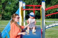 Het jonge mooie moeder en dochter gelukkige de familie van het babymeisje spelen op de schommeling, en rit in pretpark het glimla Royalty-vrije Stock Foto's