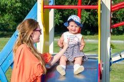 Het jonge mooie moeder en dochter gelukkige de familie van het babymeisje spelen op de schommeling, en rit in pretpark het glimla Royalty-vrije Stock Foto