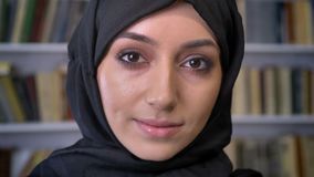Het jonge mooie moslimmeisje in hijab let neer op in boek, lettend op bij camera, godsdienstig concept, boekenrek