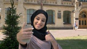 Het jonge mooie moslimmeisje in hijab maakt selfie op haar smartphone, tonend als teken in dag in de zomer