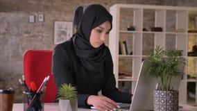 Het jonge mooie moslimmeisje in hijab werkt met laptop in bureau, het werkconcept, bedrijfsconcept, mededeling