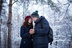 Het jonge mooie paar die elke anderen opwarmen dient sneeuw de winter bospark in Nieuwjaar, Kerstmis en de winter het concept van Royalty-vrije Stock Fotografie