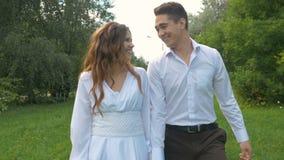 Het jonge mooie paar loopt in het park Romantische datum Zij zijn gelukkig, lachend en bekijkend elkaar stock footage