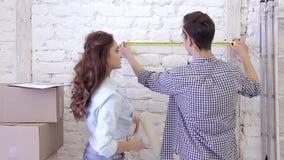 Het jonge mooie paar meet de afmetingen van muur met een meetlint stock footage