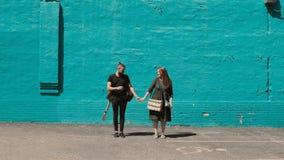 Het jonge mooie paar stellen dichtbij de heldere blauwe muur De knappe man met gitaar houdt hand van vrouw met sketchbox stock videobeelden