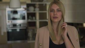 Het jonge mooie portret die van de maniervrouw camera bekijken - Kaukasisch blondemeisje die thuis biege voor jasje en zwarte opp stock footage