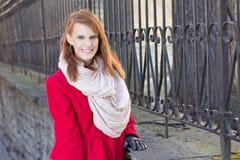 Het jonge mooie redhaired vrouw stellen dichtbij metall omheining Royalty-vrije Stock Fotografie