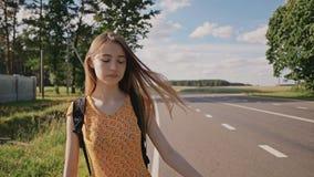 Het jonge mooie Russische meisje met lang haar in een kleding en een rugzak op haar haalt terug een auto op de snelweg zij stock video