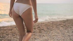 Het jonge mooie sexy gelooide meisje in bikini met blond haar is op de kust van het overzees op het strand bij zonsondergang stock footage