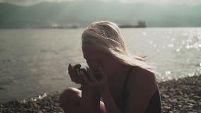 Het jonge mooie sexy gelooide meisje in een zwempak uit één stuk wast haar gezicht of strijkt zich met stenen stock videobeelden