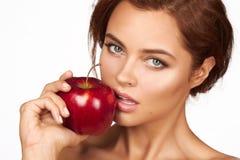 Het jonge mooie sexy meisje met donker krullend haar, naakte schouders en hals, die grote rode appel houden om van de smaak te ge Royalty-vrije Stock Foto's